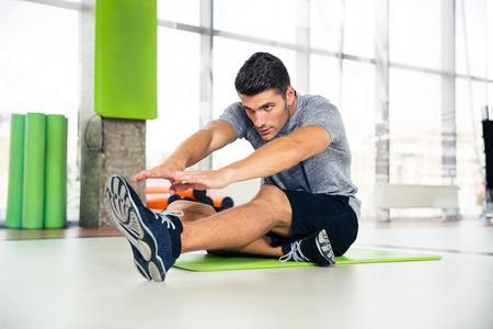 フィットネス: ジムでストレッチ体操を行うフィットネス男の肖像