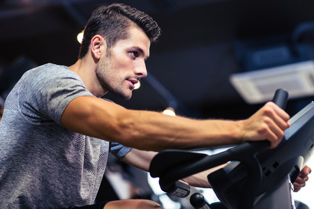 Side view portrait of a man workout on a fitness machine at gym Stock Photo