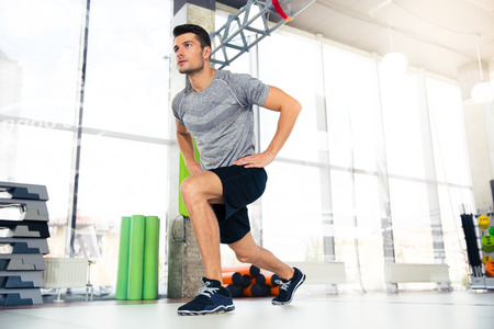 handsome young athletic: Portrait of a handsome fitness man doing warm-up exercises at gym