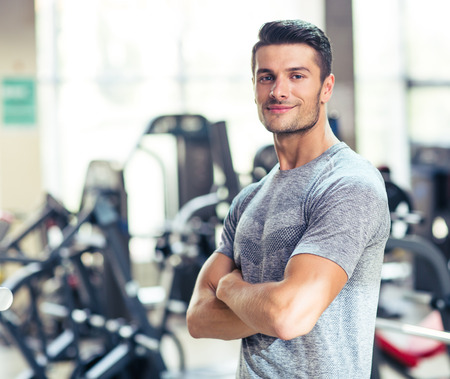 Portrait of a happy fitness man standing with arms folded at gym and looking at camera