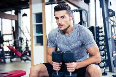 Portrait of a handsome fitness man workout with dumbbells in gym