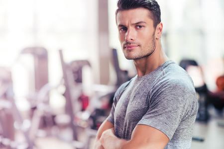 attraktiv: Portrait eines Fitness-Mann, der mit den Armen in der Turnhalle gefaltet