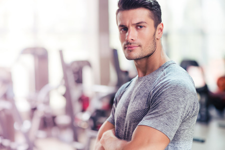 Portrait of a fitness man standing with arms folded in gym