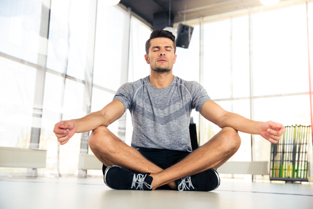 handsome boy: Portrait of a handsome man meditating in fitness gym Stock Photo