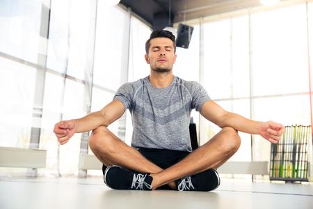 hombre flaco: Retrato de un hombre guapo meditar en el gimnasio de fitness