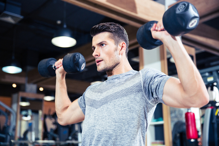 handsome young athletic: Portrait of a fitness man workout with dumbbells at gym Stock Photo