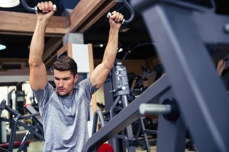 sport fitness: Portrait of a fit man workout on fitness machine in ggym Stock Photo