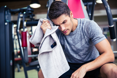 sudoracion: Retrato de un culturista guapo seca el sudor en el gimnasio de fitness Foto de archivo