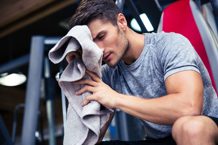 in towel: Portrait of a handsome man sitting on the bench with towel in fitness gym