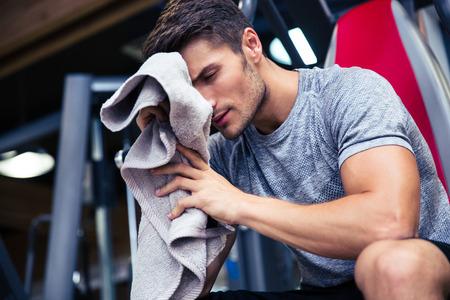 gimnasio: Retrato de un hombre guapo sentado en el banco con una toalla en el gimnasio de fitness