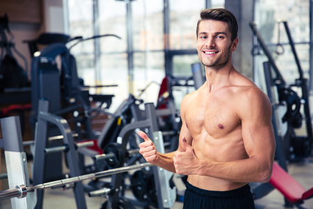 men body: Portrait of a smiling muscular man showing thumbs up at gym Stock Photo