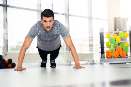 musculine: Portrait of a fitness man doing push-ups in gym