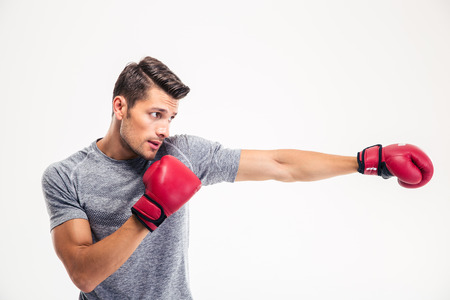 Side view portrait of a handsome man boxing isolated on a white background