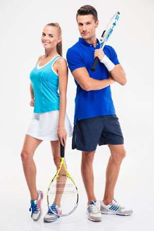 Full length portrait of a two tennis players standing isolated on a white background and looking at camera