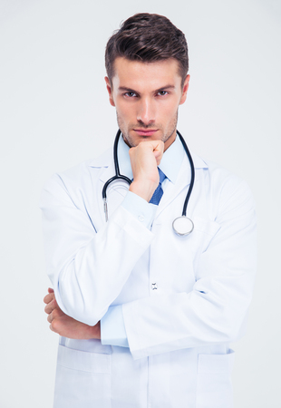 Portrait of a pensive male doctor looking at camera isolated on a white background
