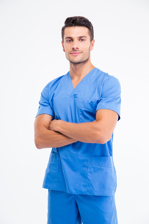 Portrait of a handsome male doctor standing with arms folded isolated on a white backgorund. Lookign at camera Stock Photo