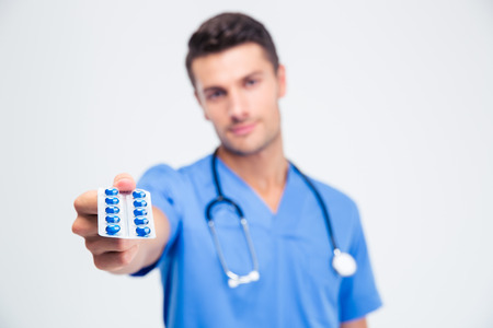 doctor holding pills: Portrait of a male doctor holding pills isolated on a white background. Focus on pills