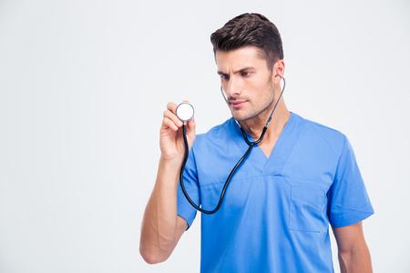 estetoscopio: Retrato de un médico sosteniendo el estetoscopio masculino aislado en un fondo blanco Foto de archivo