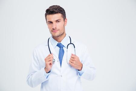 흰색 배경에 고립 된 청진 기 함께 서있는 남성 의사의 초상화