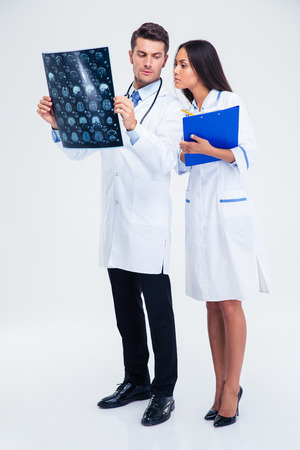 Full length portrait of a two medical workers looking at x-ray picture of brain isolated on a white background Stock Photo