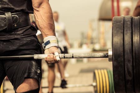 Närbild porträtt av professionell bodybuilder träning med skivstång utomhus Stockfoto