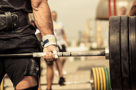 Closeup portrait of professional bodybuilder workout with barbell outdoors