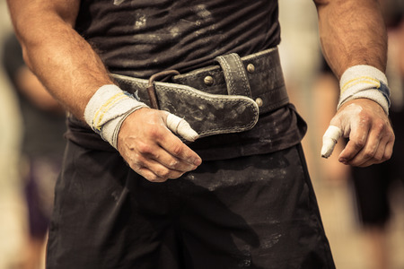 bodybuilder: Closeup portrait of a bodybuilder girding on his bodybuilding belt