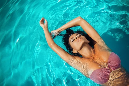 Portrait of attractive woman relaxing at swimming pool