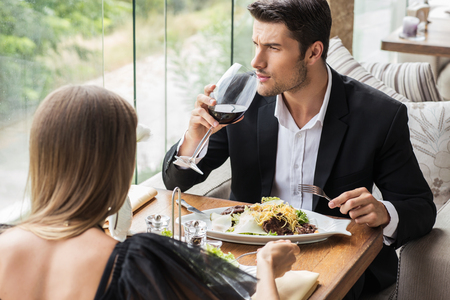 romantic date: Portirat of a beautiful couple drinking wine in restaurant