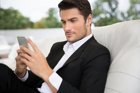 donna ricca: Ritratto di un uomo bello con all'esterno di smartphone in ristorante Archivio Fotografico