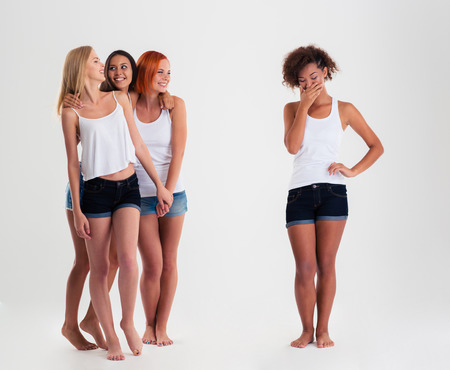 sad lady: Upset afro american women standing while friends laughing with her isoalted on a white background
