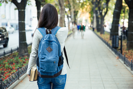 books: Back view portrait of a female student walking in the city park outdoors