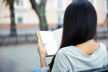 Back view portrait of a woman reading book outdoors Imagens