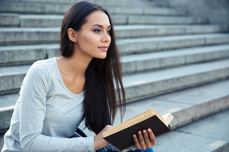 autodidact: Portrait of a charming young woman sitting on the city stairs with book outdoors Stock Photo