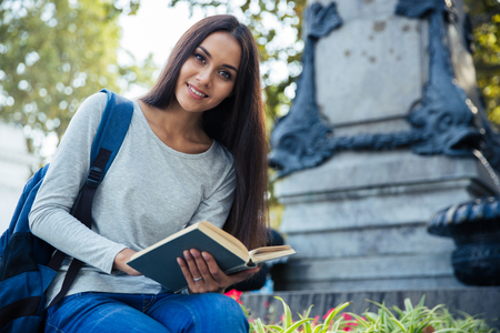 autodidact: Portrait of a cheerful female student holding book and looking at camera outdoors