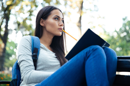 autodidact: Portrait of a thoughtful female student sitting on the bench with book outdoors