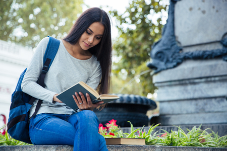 autodidact: Portrait of a happy female student reading book outdoors