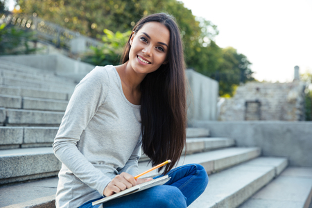 college campus: Portrait of a smiling girl sitting on the city stairs with pencil and notepad outdoors and looking at cmaera