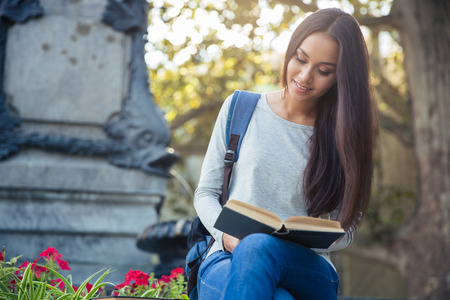 autodidact: Portrait of a smiling girl reading book outdoors