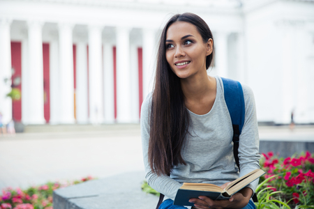 autodidact: Portrait of a smiling female student holding book and looking away outdoors