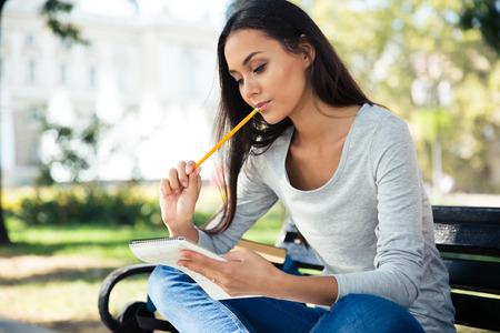 ペンとメモ帳の屋外でベンチに座って思慮深い女性の肖像