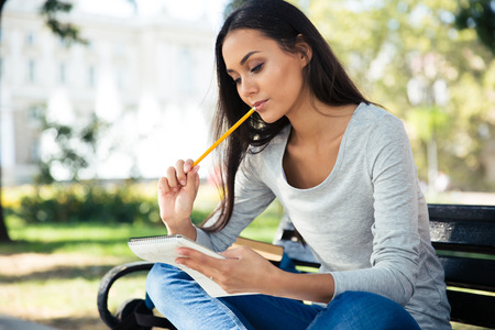 Portrait of a thoughtful woman sitting on the bench with pen and notepad outdoors Imagens - 45835372