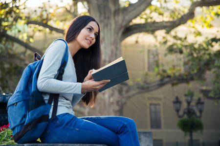 autodidact: Portrait of a thoughtful female sutdent holding book and looking up outdoors
