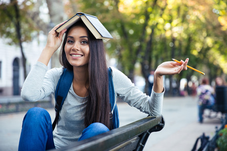 Portrait of a happy funny girl sitting on the bench with book on head outdoors and looking at camera
