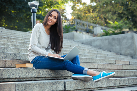 Portrait of a smiling female student sitting on the city stairs and using laptop computer outdoors Banque d'images