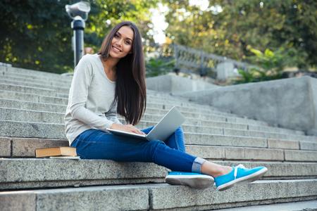 Retrato de un estudiante sonriente sentado en las escaleras de la ciudad y que usa el ordenador portátil al aire libre Foto de archivo - 45835389