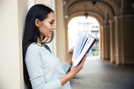 Portrait of a beautiful woman reading book outdoors