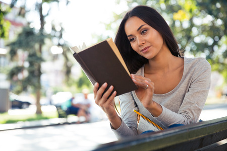 autodidact: Portrait of a happy young woman reading book on the bench outdoors Stock Photo