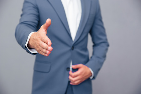 one person only: Closeup portrait of a businessman stretching hand for handshake over gray background