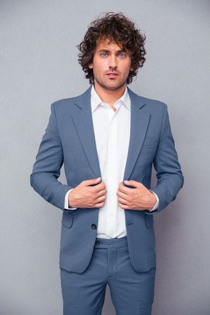 man hair: Portrait of a confident businessman standing over gray background and looking at camera